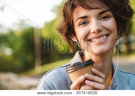 Image of cheerful caucasian woman 20s wearing denim jacket smiling while drinking takeaway coffee and using earphones during walk through green park
