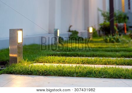 Ground Lantern Lighting Marble Walkway In The Evening Park With A Green Lawn, Closeup Lantern Illumi