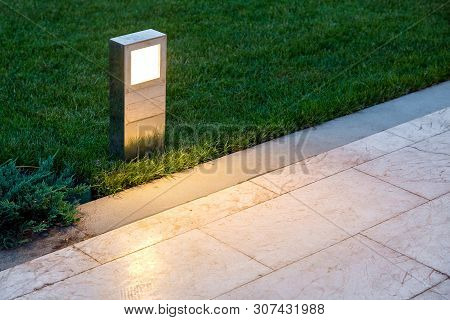 Ground Lantern Lighting Marble Walkway In The Evening Park With A Green Lawn, Closeup Lantern Illumi