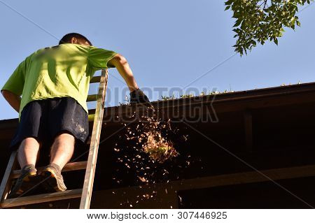 An Unidentified Man Stands On An Extension Ladder Cleaning The Eaves And Gutters Of A Two Story Hous