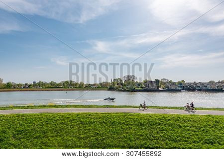 Capelle Aan Den Ijsel, Rotterdam, Netherlands - April 22, 2019 : People Cycling By The Ijsel Canal I