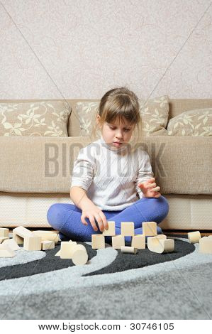 The Little Girl Plays Wooden Toy Cubes