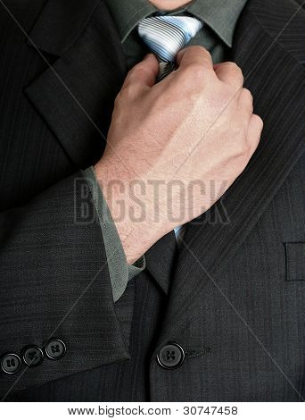 Businessman tweaking his tie with a hand poster