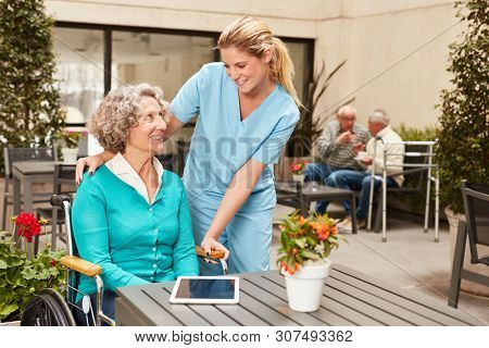 Caregiver takes care of a woman in a wheelchair in a rehab or nursing home