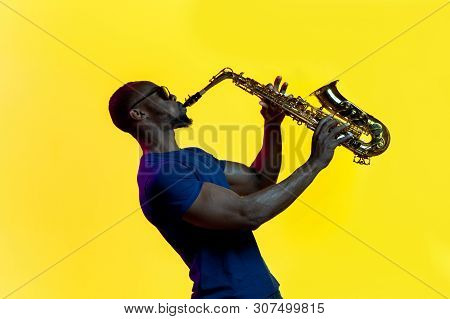 Young African-american Jazz Musician Playing The Saxophone On Yellow Studio Background In Trendy Neo