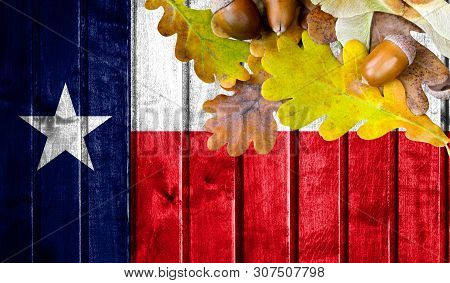 State Of Texas Flag On Autumn Wooden Background With Leaves And Good Place For Your Text.
