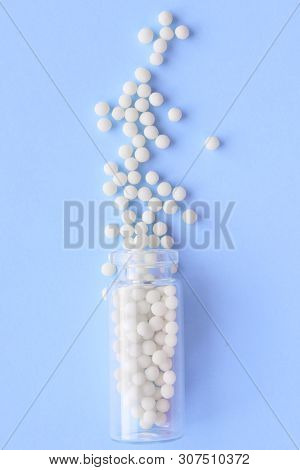 Close Up Homeopathic Globules And Glass Bottle On Blue Background. Alternative Homeopathy Medicine H