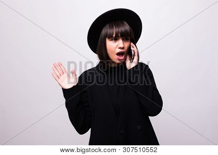 Portrait Of Shocked Young Woman In Black Hat Talking On Mobile Phone Isolated Over White Background