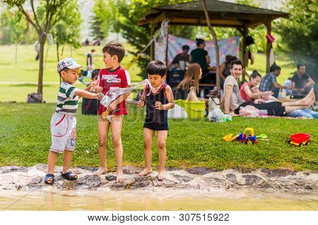 Eskisehir, Turkey - May 24, 2015: Kids Playing With Water Near Their Families. People Having Picnic