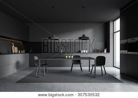 Interior of stylish kitchen with gray walls, concrete floor, gray countertops and cupboards, table standing on carpet and dark gray cupboard with ovens. 3d rendering poster