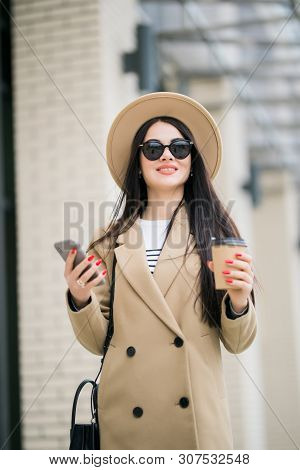 Young Pretty Woman Use Phone While Walking To Work Drinking Coffee On Morning Commute In City