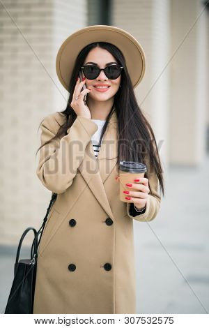 Young Smiling Business Woman In Sunglasses And Coat Stands Near Office Centre With Cup Of Coffee And