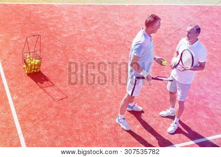 Full length of men talking while standing on tennis court during match