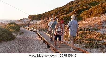 Group Of Senior Friends Walking Along Boardwalk At Beach On Summer Group Vacation