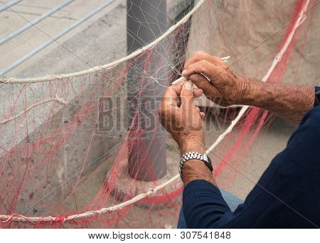 Old Fisherman Reparing Fishing Net During The Day.