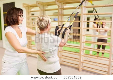 Personal trainer or physiotherapist gives senior help in sling training