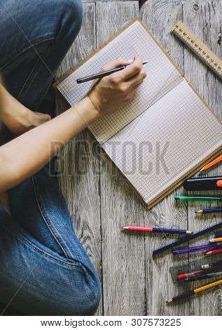 Right-handed Woman Holding Pen While Writing On Small Notebook On Wooden Floor