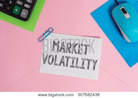 Conceptual hand writing showing Market Volatility. Business photo showcasing Underlying securities prices fluctuates Stability status Wire electronic mouse calculator paper colored background. poster