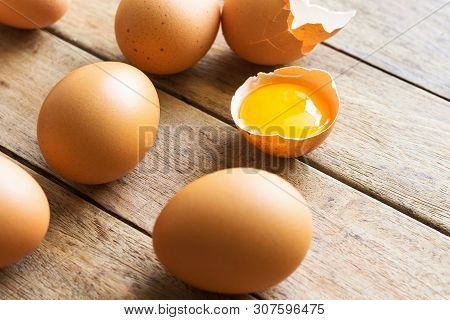 Organic Whole And Cracked Free Range Brown Eggs With Bright Sunny Glossy Yolk On Aged Wood Kitchen T