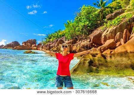 Happy Caucasian Young Woman With Open Arms On Turquoise Waters At Anse Cocos Near Grande Anse And Pe