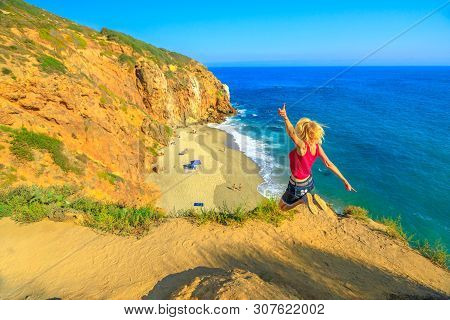 California Travel Destination Concept. Lifestyle Woman Jumping On Pirates Cove Promontory, A Small C
