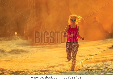 Sport, Outdoor Life And Healthy Lifestyle Concept. Happy Blonde Woman Running On Seashore Of El Mata