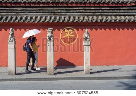 Chengdu, Sichuan Province, China - June 6, 2019 : People With Umbrella Walking By A Red Wall Surroun