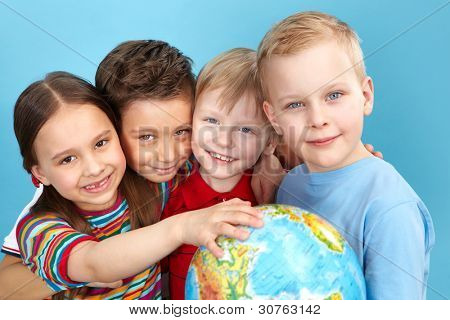 School children holding a globe looking at camera positively
