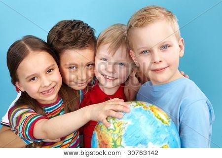 Schulkinder holding a Globe, Blick in die Kamera positiv
