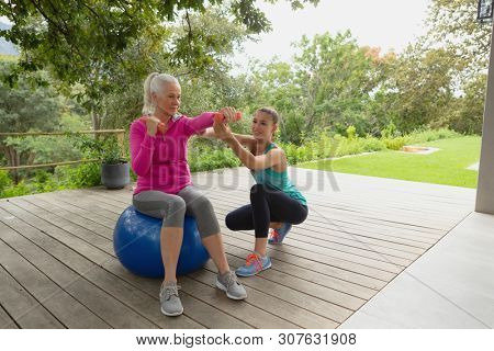 Front view of beautiful Caucasian female trainer assisting active senior Caucasian woman to exercise with dumbbells in the porch