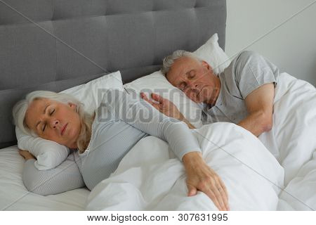 Front view of active senior Caucasian couple sleeping together in bed in bedroom at home