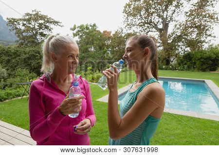 Side view of beautiful Caucasian female trainer and active senior Caucasian woman drinking water in the backyard
