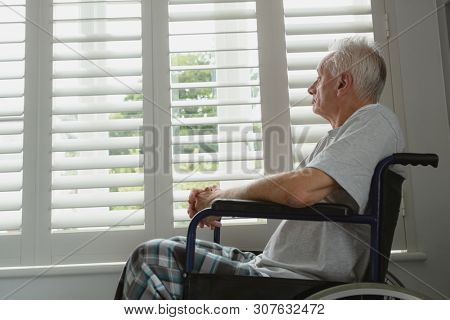Side view of thoughtful active senior Caucasian man in wheelchair looking through window at home