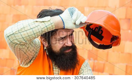 Hard Work At A Construction Site. Heavy Profession. Male Builder Wipes Sweat From Brow. Tired Builde