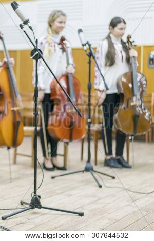 Childrens violin ensemble. Children with violins on stage. Childrens initiative, small talents. Early child development. Blurred poster