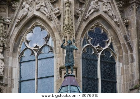 Two symmetrical Gothic-style church windows with statue poster