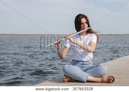 A Beautiful Woman Posing In Beach While Playing On A Flute.