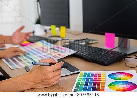 Graphic Design With Color Swatches And Tablet On A Desk. Graphic Designer Drawing Something On Table