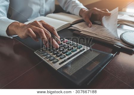 Woman With Bills And Calculator. Woman Using Calculator To Calculate Bills At The Table In Office. C