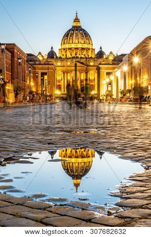 Vatican City By Night. Illuminated Dome Of St Peters Basilica And St Peters Square. Group Of Tourist