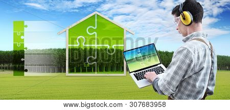 Green House Construction Renovation Concept Handyman Carpenter Man With Laptop Computer And Puzzle I