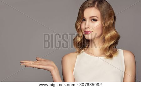 Woman  Smiles Surprise Showing Product .beautiful Girl With Curly Hair Pointing To The Side . Presen