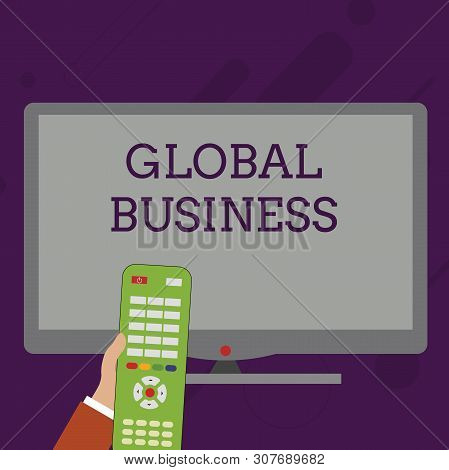 Word writing text Global Business. Business concept for Trade and business system a company doing across the world Hand Holding Computer Remote Control infront of Blank Wide Color PC Screen. poster