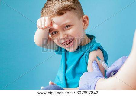 Vaccination Concept. Female Doctor Vaccinating Cute Little Boy On Blue Background, Closeup