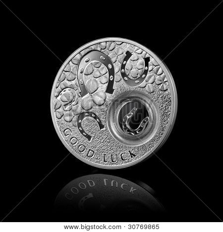 silver coin with horseshoes isolated on black