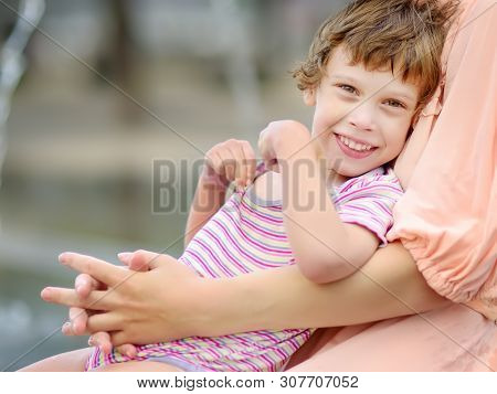 Close-up Portrait Of Beautiful Disabled Girl In The Arms Of His Mother Having Fun In Fountain Of Pub