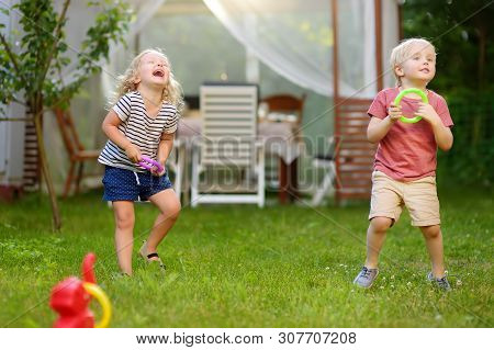 Cute Little Boy And Girl Playing In Game Throwing Rings At Summer Outdoors. Games For Family With Ki
