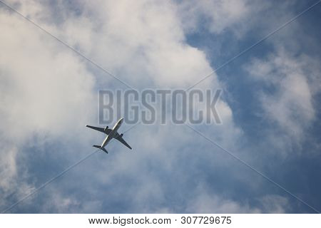 Airplane Flying In Blue Sky On Background Of White Clouds. Silhouette Of A Commercial Plane, Turbule