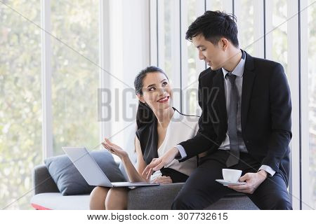 Asian Business People Using Laptop, They Sitting On Sofa In Office, Woman Presenting Her Report By L