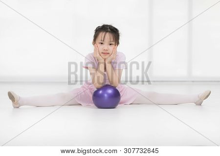 Cute Asian Girl In Pink Dress Is Posing And Holding Purple Gymnastic Ball In Front Of Window.